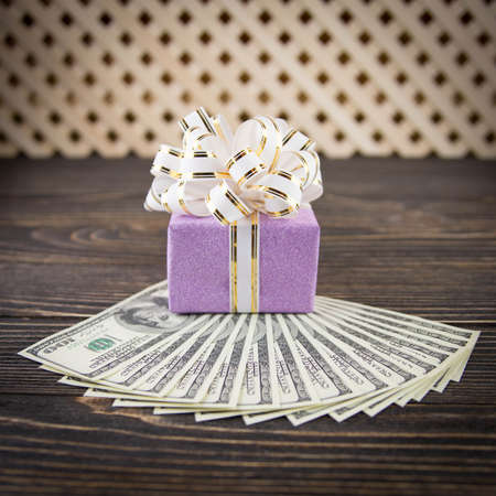 Dollars anf gift box on wooden background photo