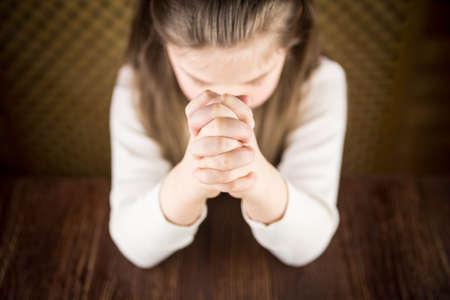 religion catolica: La ni�a reza en una mesa