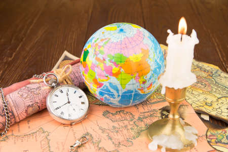 The globe, ancient cards with a pocket watch and a candle photo