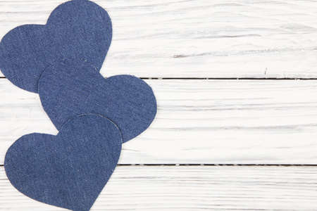 Jeans texture in Heart shapes on wood background photo