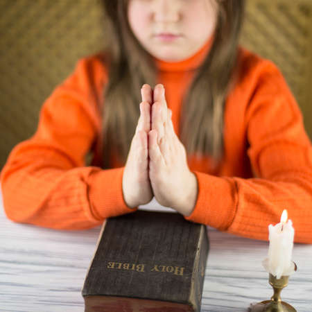 The girl prays at a table photo