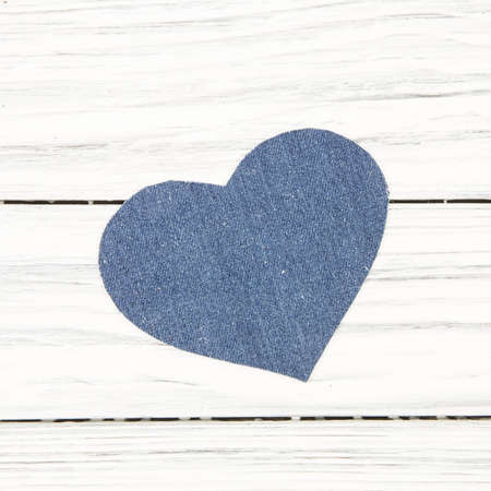 Jeans texture in Heart shape on wood background photo