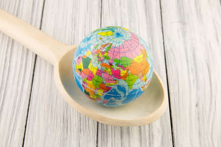 Globe in a wooden spoon on a old background photo