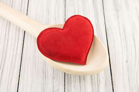 Red heart in a wooden spoon on a old background photo