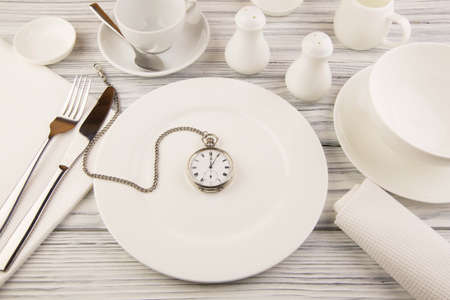 Ware for food white on a wooden table with pocket watch photo