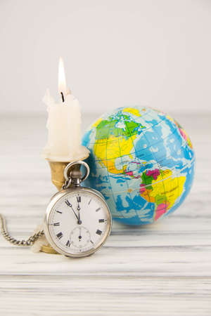 The globe with a pocket watch and a candle photo