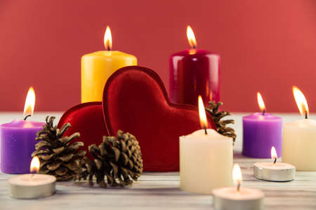 fir-tree cones and candles on a wooden background photo