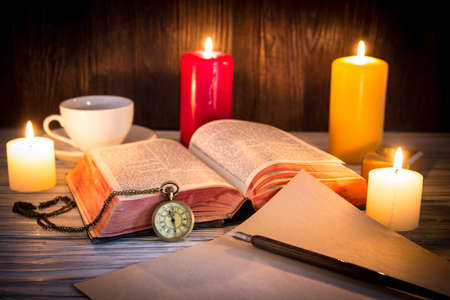 open bible: Candle and bible on wood background