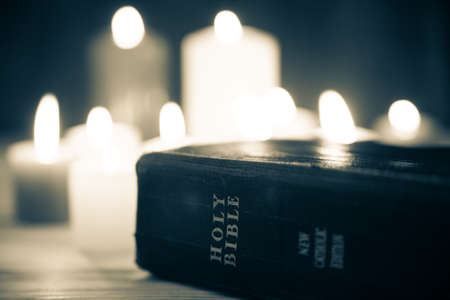 christian candle: Candle and bible on wood background