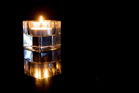 candela: Candele in portacandele di vetro su sfondo nero.