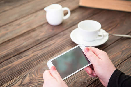 The smartphone and cup of coffee on an old wooden table photo