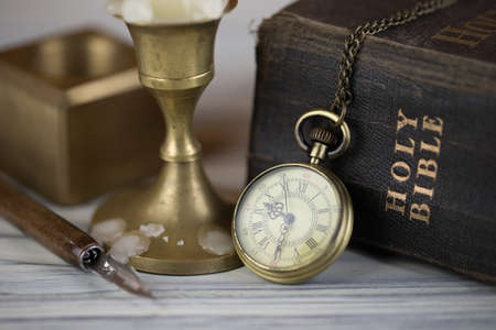 Pocket watch candle and Holy Bible Stock Photo