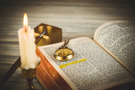 Pocket watch candle and Holy Bible Imagens
