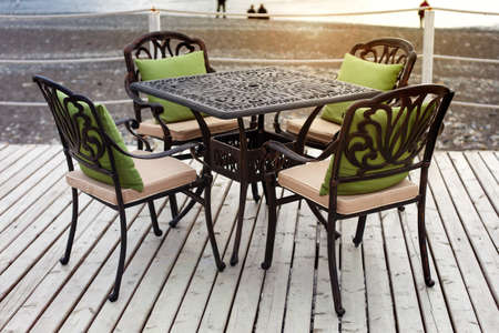 stoop: A table in a cafe on the beach at sunset Stock Photo