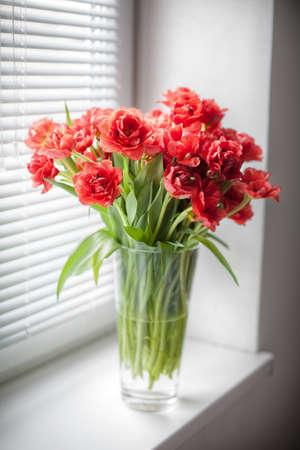 ブラインドのある窓にチューリップの花束