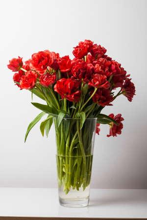 ガラス花瓶をテーブルの上に赤いチューリップ