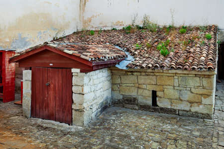 Old rustic building of stone with a tiled roof with moss