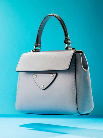 Stylish leather womens handbag on a blue background
