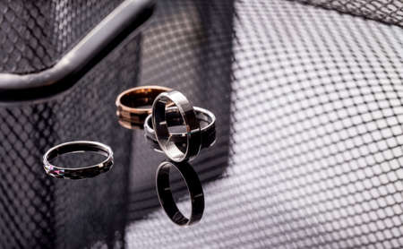 Group of beautiful jewelry rings in gold, silver, platinum closeup on a table with reflection and with a fashionable gray background