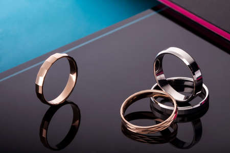 A set of wedding rings with precious stones. On fashionable black glossy background with reflection