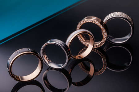 A group of beautiful engagement rings with diamonds on a black background. Closeup, gold, silver, platinum, brilliant