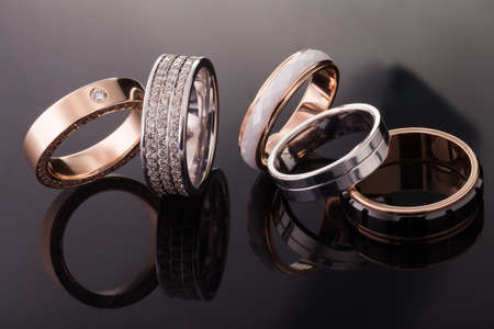 Silver, gold, platinum rings of different styles on the dark background of reflections 写真素材