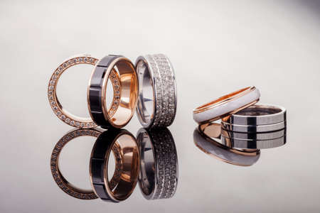Silver, gold, platinum rings of different styles on the gray background of reflections