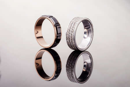 Two gold wedding rings with diamonds with reflection on gray background, close up