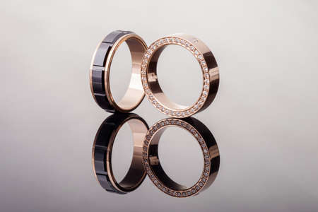 Two gold wedding rings with diamonds and black ceramic closeup with reflection 写真素材