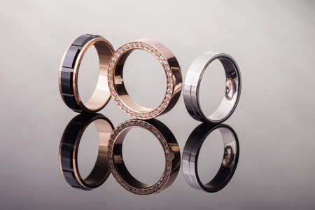 Group of wedding rings of different styles with diamonds on a glossy background, isolated, closeup 写真素材