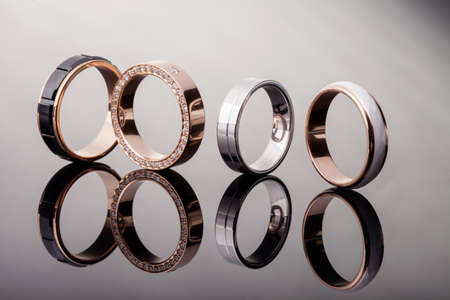 A group of engagement diamond wedding rings on a glossy background, isolate, closeup 写真素材