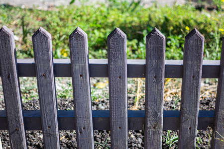 Small wooden fence with rusted nails, with grass in the background