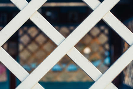 latticed: Chain link fencing behind a wooden lattice.