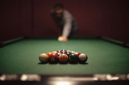 American billiard poule. Shot of a man playing billiard. Triangle of billiard balls.