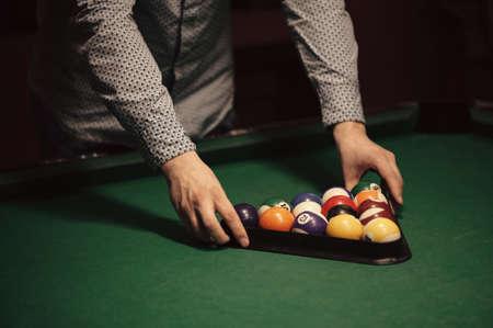 American billiard poule. Triangle of billiard balls. A man getting ready to start a game of billiards.