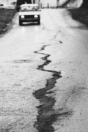A crack on the asphalt and a traveling car in front. Black and white photography. Conceptual.