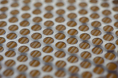 Grid with round perforation. Metal holes on an orange background. Oil filter close-up. Stock Photo