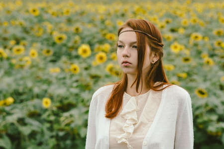 art processing: Delicate portrait of a red-haired girl dressed in a vintage style against the background of a field with sunflowers. Artistic processing. Natural make-up. Stock Photo