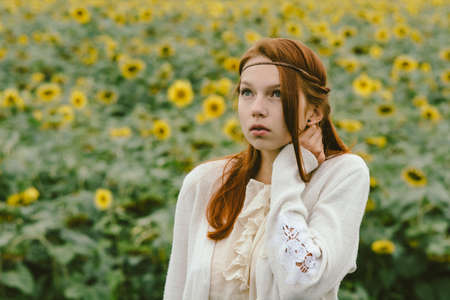 art processing: Elegant red-haired girl with natural make-up and piercing in the background of a field of sunflowers.