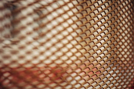 Wall of a city building through a mesh fence. Rusty netting. Picturesque. Stock Photo