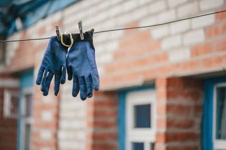 Working blue gloves hang on a rope, attached with clothespins, against the backdrop of a brick house. Stock Photo