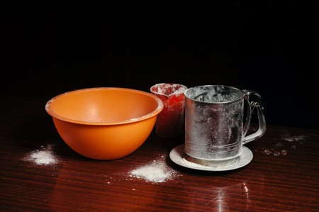 Orange cup, measuring cup, and a steel sieve stand on a wooden table on a black background. Flour. Stock Photo