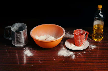 Orange cup, measuring cup, and a steel sieve, sunflower oil stand on a wooden table on a black background. Flour.