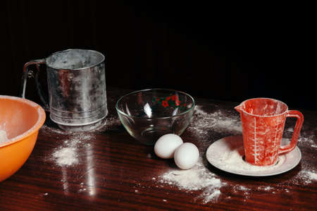 measuring cup: Orange cup, measuring cup, and a steel sieve, two eggs stand on a wooden table on a black background. Flour.