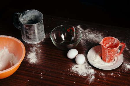 Orange cup, measuring cup, and a steel sieve, two eggs stand on a wooden table on a black background. Flour.