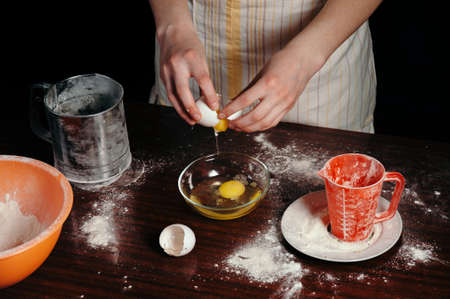 A girl in an apron in a dark kitchen breaks the egg into a bowl.