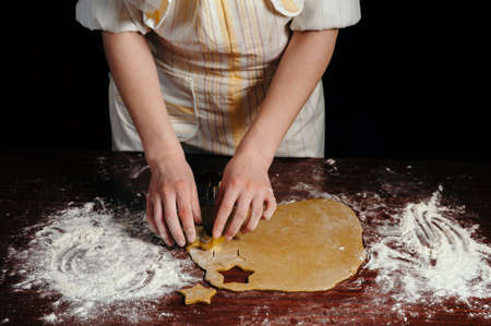 The girl in an apron cuts dough shaped cookies in the form of stars on a wooden table. Close-up. Stock Photo