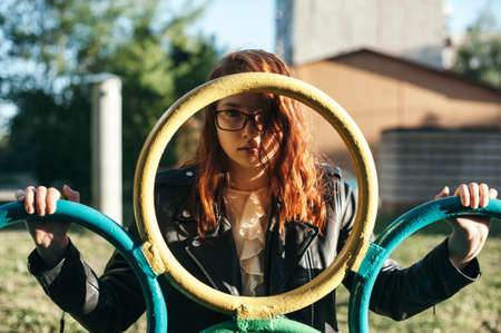 guadaña: Portrait of a red-haired girl with red glasses on a playground. The girl looks through the iron circle. Foto de archivo