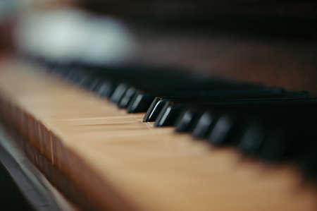 Sleutels van een oude piano in vervaging. Muzikaal oud instrument met een houten hoesje. Wijnoogst.