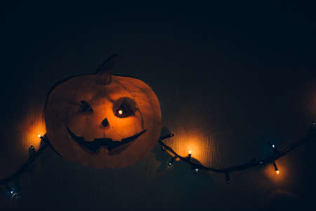 A paper pumpkin with a flashing garland in place of the eyes, hanging on the wall. A horrible template for Halloween.